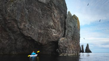 Sea kayaking near a dramatic coastline near Trinity, Newfoundland, Canada.
